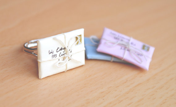 etsylady:  £7.00 GBP   Letter Envelope Rings in Pastel Colours, Tied With String Adorable little paper envelopes based in clay for strength and survival, with a tiny stamp and address, tied with string to complete the look.Lately I've been looking a lot at envelopes and letters. I've seen some pictures posted on Tumblr of some adorable old envelopes, and I tried for something myself. I am a little disappointed because there was more detail in my mind with these pieces, but, as usual, whatever that detail was, I never figured it out. http://www.etsy.com/listing/81090484/letter-envelope-rings-in-pastel-colours?ref=pr_shop