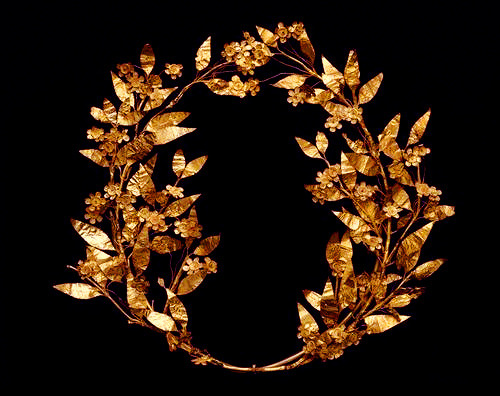 Greek myrtle wreath, c. 330-250 BC.  In ancient Greece, wreaths made from plants like laurel, ivy, and myrtle were awarded to athletes, soldiers, and royalty. Similar wreaths were designed in gold and silver for the same purposes or for religious functions. This example conveys the language of love. A plant sacred to the goddess Aphrodite, myrtle was a symbol of love. Greeks wore wreaths made of real myrtle leaves at weddings and banquets, received them as athletic prizes and awards for military victories, and wore them as crowns to show royal status.  By the Hellenistic period (300-30 BC), the wreaths were made of gold foil; too fragile to be worn, they were created primarily to be buried with the dead as symbols of life's victories. The naturalistic myrtle leaves and blossoms on this wreath were cut from thin sheets of gold, exquisitely finished with stamped and incised details, and then wired onto the stems. Most that survive today were found in graves.