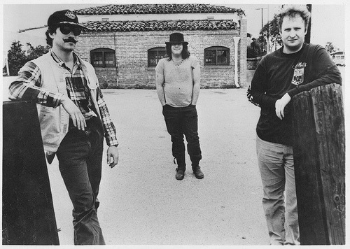 "Husker Dü. They really need no introduction, so consider this post more of a love letter to one of the most influential bands of the last 30 years (who just happens to have two queer members (thanks lookuplookup!) Score!) Sadly, Husker Dü was only around for 9 years, but in that relatively short amount of time they played a significant part in reshaping punk music and creating the foundation for emo, queercore, some modern pop-punk, and a ton of indie-tinged subgenres. They started out as a punk band influenced by the seminal acts of the time-The Dead Kennedy's, Black Flag, and the like. It was a pretty classic hardcore punk sound, short, harsh songs with gruff vocals and even gruffer chords. What set them apart, however, was the use of far more personal, rather than political or social justice oriented, lyrics. This would eventually become a staple of the hardcore offshoot, emo, with bands like Embrace and Rites of Spring. But Husker Dü really made their mark beginning in 1984 with their album Zen Arcade. Much of the intensity and punk passion was still present, but the band began to introduce far more melodic instrumentals, like on ""What's Going On (Inside of My Head)."" By the time of their 1985 album, New Day Rising, they were sounding a decade ahead of their time. ""I Apologize"" sounds like it could have been off of an early Get Up Kids or Jawbreaker album, even a gruffer version of a Promise Ring song. It's all full of riffs that stick in your brain and lyrics that pull at your heart. Without Husker Dü we wouldn't have Lemuria, Superchunk, most of that mid-90s emo I love so much, like The Get Up Kids and Jimmy Eat World, Team Dresch, Sleater-Kinney, and a whole host of other bands that I (and likely you as well, if you read this blog regularly) love. We owe Bob Mould and company a whole debt of gratitude, and what better way to do that then cracking out Zen Arcade  for old time's sake?"