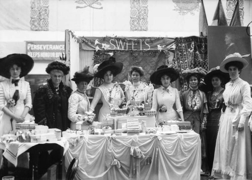 edwardianpromenade:  The sweets stall at The Women's Exhibition, Prince's Skating Rink, May 1909. The Women's Exhibition, was organised by the Women's Social and Political Union primarily as a fund-raising event. Over fifty stalls, decorated in purple, white and green displayed a variety of items for sale that had been donated or made by suffragettes. Alongside the suffragettes running the sweets stall, can be seen Emmeline Pankhurst, to the right of the image. At the top a partial view of the murals designed by Sylvia Pankhurst that decorated the walls of the hall. ©Museum of London