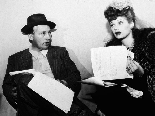 Lucille Ball and Bing Crosby sit with scripts in their laps, circa 1945.