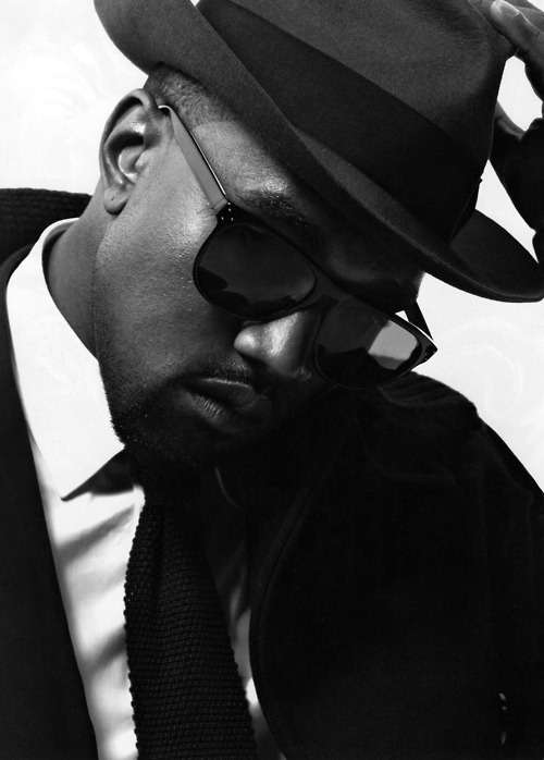 cirq6:  The Style Of Mr West The last time we profiled Kanye, we discussed his evolution in style as representative of the evolution experienced by many hip hop luminaries and how that style reflected their understanding of their business as it fit symbiotically within the ecosystem of a wider economic reality. This image though is much more than a photograph. For many who either follow or chronicle (or both) hip hop, their connection no matter how knowledgable is still hopelessly superficial, driven by a love of the outrageous, the overt and the attendant 'look,pose,cameraflash!' of the lifestyle and therefore, this image will say very little. For the purists however, who understand that the collective lyrical output of hip hop is as much driven by social condition as it is by the psychological state of the messengers themselves, this image speaks the equivalent length of War and Peace for it says that this messenger has reached a state of sartorial comfort and thus, expresses his persona in ways which even though they are varied, are as calmly confident as this ensemble. Much like a fencer then, who thrusts his epee for the 'kill' only when he is fully balanced, coiled, ready and having parried the early frenzied attempts of his attacker, clearly perceptive of his own opening to strike, Kanye now enters a stage where he is driven by a matured sense of his place in the hip hop firmament and the world at large. This image suggests that unlike a brainwashed world that has been conditioned to believe that great music in this genre must be the result of the poverty, crime and psychologically angry circumstance of the messenger, Kanye's music can now be more powerful, dynamic, varied and expressive; reflective of his understanding of himself. Yeah, for many it's either just a photograph or the writer's giddy adulation of Kanye; far from it!  Instead, we at C6 trust that eventually, those who think so will learn how to perceive the 'story' of the photographed image and thus understand that all images are frozen moments in time that capture not just a look but a deeper personal reality that we all exude like a synonymous soundtrack to our lives…