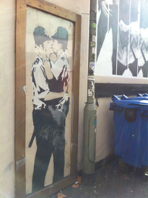 A framed Banksy by the bins.  In other news, I've just had the best sausage roll of my life.  Make of that what you will.