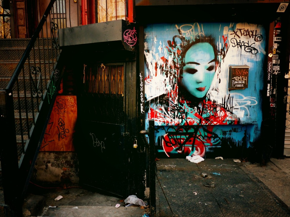 "nythroughthelens:  Street art on a store gate. Lower East Side, New York City. Layers of paint, grit, decay and meaning make me fall in love with New York City over and over again. Elaborate painted dreamscapes unfold on slumbering store gates surrounded by the discarded remnants of  every yesterday and today. —- View this photo larger and on black on my Google Plus page —- Buy ""Urban Fragments - Lower East Side - New York City"" Posters and Prints here, View my store, email me, or ask for help."