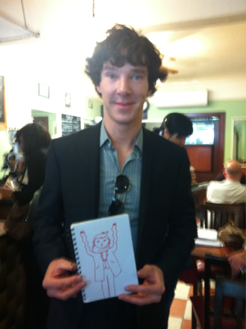 Benedict Cumberbatch, busy breaking the fourth wall in a cafe with this doodle that someone drew for him, based on the Sherlock fan-comics by Geothebio.