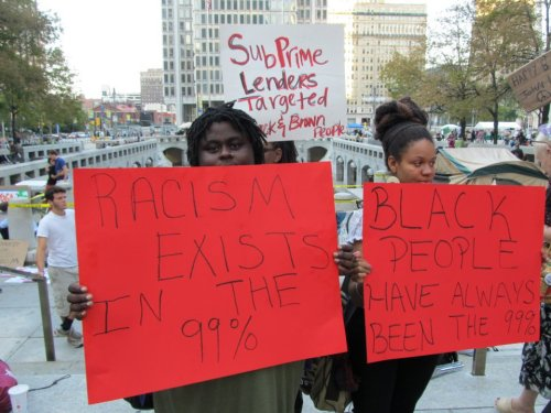 complex-brown:  BLACK OUT! Occupy Philadelphia Racism Exist in the 99 % Black People Have always been in the 99 % And my sign is hidden a little, but it reads : SubPrime Lenders targeted Black and Brown People.