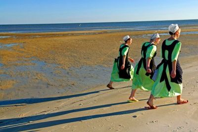 Amish women walk on a beach in Waveland, Mississippi. Photograph by Johnny Nicoloro, National Geographic