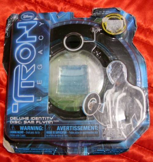 Deluxe Identity Disk: Sam FlynnMovie: TRON: LegacyBrand: Spin MasterYear: 2010Description: Sam Flynn's ID Disk from the movie. It is used for recording data in the TRON system.Additional information: I didn't opened it because it was a gift for a friend, but I wanted to post the info anyways. The package is a little bit damaged but the disk batteries are still working XD.