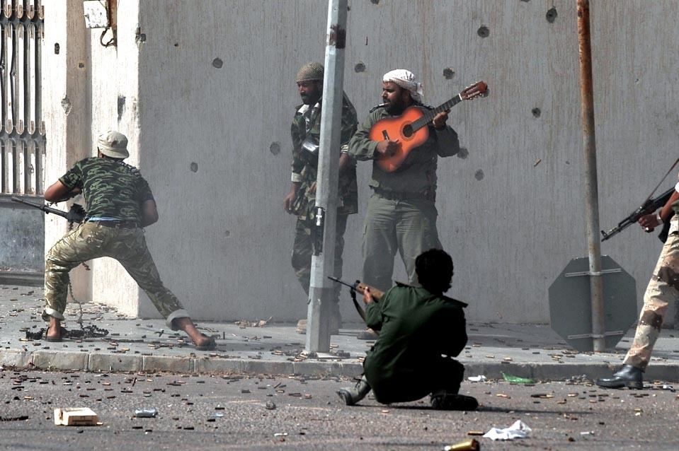inothernews:  SERENADE / FUSILLADE    Revolutionary forces fired their weapons at fighters loyal to Col.  Moammar Gadhafi as a comrade played a guitar in Sirte, Libya, Monday.  (Photo: Aris Messinis / AFP-Getty via the Wall Street Journal)