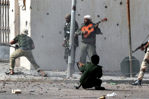 "Guitar Hero ""Libya's new regime forces fire their weapons at fighters loyal to fugitive strongman Moammar Gadhafi as a comrade plays a guitar during a battle in Sirte on Oct. 10, in a drive to control Gadhafi's hometown after a month-long siege"". That is one spoony bard. (via: photoblog.msnbc)"
