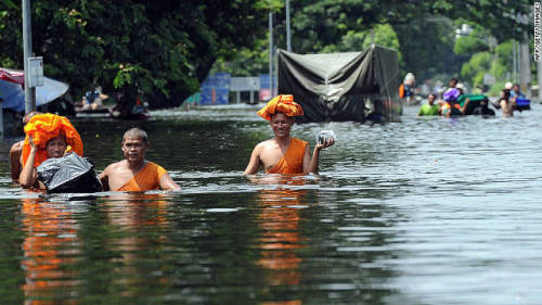 Buddhist monks walk through chest-high water as floods inundate Ayutthaya province in Thailand on Monday.  Flooding during an unusually heavy monsoon season has caused nearly 500 deaths to date and millions of evacuations in Thailand and neighboring Cambodia.  (Photo: AFP-Getty via CNN)