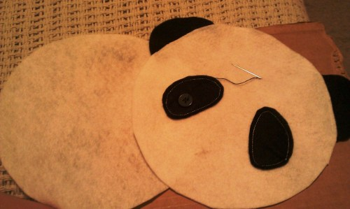 Finding so many panda crafts and felties on both Etsy.com and Pinterest.com, I thought I'd give it a try.  Luckily I had the exact amount of white/black felt. So here goes….I busted out the protractor again to have a perfect-ish circle and the kindergartner helped me cut out the cardstock patterns.