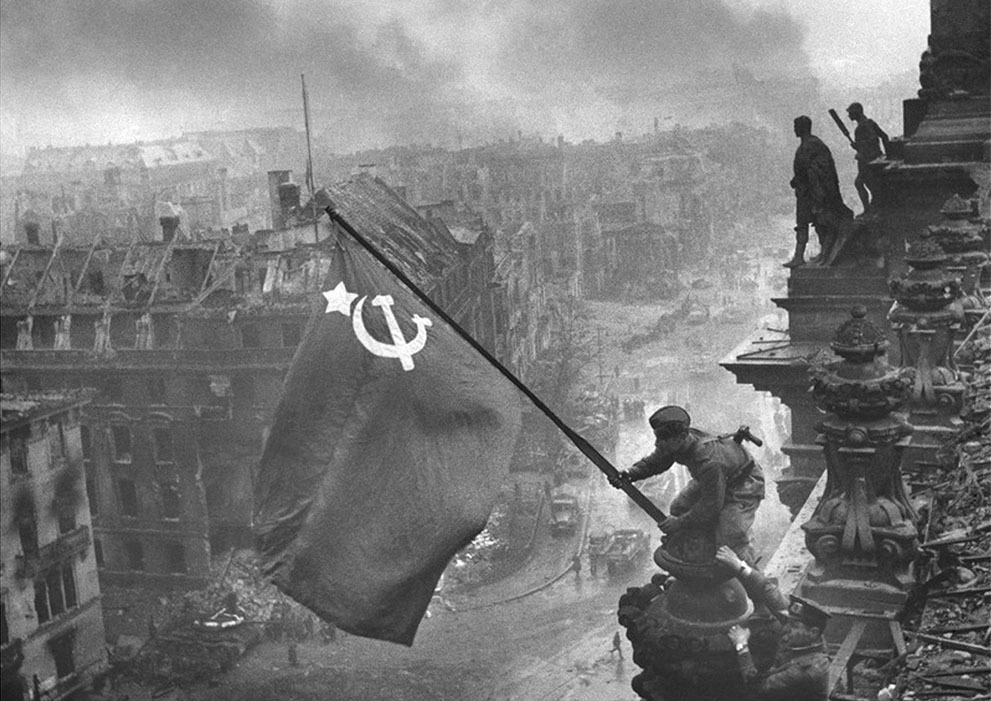"The Fall of Nazi Germany  ""Raising a flag over the Reichstag"" the famous photograph by Yevgeny Khaldei, taken on May 2, 1945. The photo shows Soviet soldiers raising the flag of the Soviet Union on top of the German Reichstag building following the Battle of Berlin. The moment was actually a re-enactment of an earlier flag-raising, and the photo was embroiled in controversy over the identities of the soldiers, the photographer, and some significant photo editing. (Yevgeny Khaldei/LOC)  See more photos here and check out the rest of In Focus's excellent World War II retrospective."