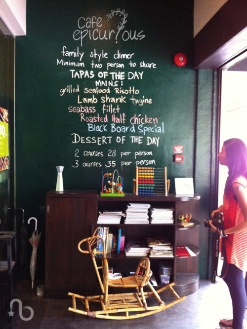 Chalkboard-style menu and rattan rocking horse at Cafe Epicurious