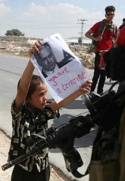 somaliadeepinmyheart:   Palestinian boy shows an Israeli soldier a portrait of Israeli Prime Minister Benjamin Netanyahu during a protest in the West Bank village of Maasarah.  Ya' allah my heart! subhanallah
