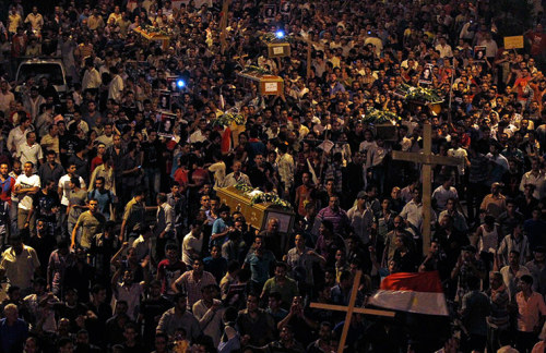 """Cairo, Egypt: Coptic Christians carry coffins as they make their way to Abbasaiya cathedral during a mass funeral for victims of sectarian clashes with murder committed by soldiers and riot police after a protest about an attack on a church in southern Egypt"" By: Mohamed Abd El Ghany/Reuters"