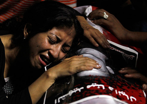 """Cairo, Egypt: A woman mourns on the coffin of Coptic Christian Mina Daniel, who was killed during clashes with soldiers and riot police on Sunday"" By: Mohamed Abd El Ghany/Reuters"