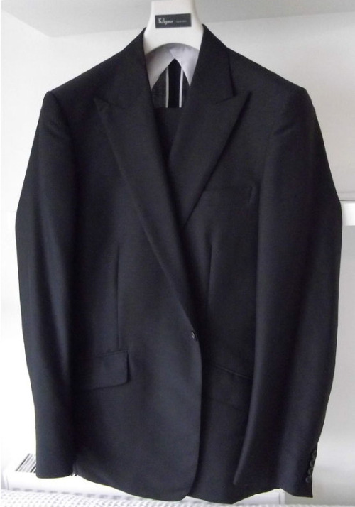 "I've written before about why black suits are generally unsuitable during the day. They're severe, they make you look like a clergyman or undertaker, they're not particularly appropriate for business and they make most men look at least a little sickly. At night, though, it's a different story. That's where a black suit like this one I spotted on eBay can really come into its own. Some of the details of this suit suggest evening wear - it has a single button-front and is single-breasted with peak lapels. Those say ""formal"" and ""evening."" They're features of the formal suit, or of the tuxedo. This guy doesn't have satin or grosgrain lapels, though, and its slanted, flapped pockets make clear it's a suit. It's made of mohair, which is lightweight and has a slight sheen. That sheen could be a liability during the day, but at night it's welcome. What you get, then, is an elegant suit for evening occasions that don't call for black tie. An important dinner, a play, an opening. Events that require a dressed-up outfit, a little panache, but not a tuxedo and not business garb. Of course, one can move further down the road to casual as the event requires, from a minimalist notch-lapel black suit all the way to, say, black boots, dark jeans and a black cashmere sweater. Or even a black leather jacket. Black, while unsuitable during the day, is the color of evening elegance - no matter how formal the occasion."