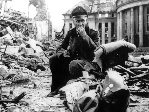 A German officer eating army rations, surrounded by the bombed out ruins of a city. Saarbrücken, Germany - Spring, 1945.