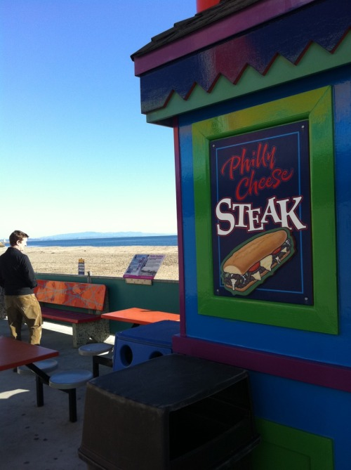 "Submitted by Amanda R.Found on the boardwalk in Santa Cruz, CA.  Two word name? Wrong color cheese? Just wrong for there to be mountains and the pacific near a place serving ""Philly"" cheesesteaks. — Amanda  I don't want anything that looks like that illustration. From what I've seen, California produces the biggest offenders. Also, what's with that typography? Looks like ""Philly Cheese"" is an adjective in itself, lol."