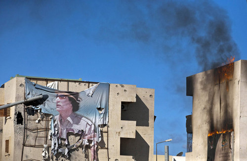 Photograph: Majid Saeedi/Getty Images Gallery from Libya: on the frontline in Sirte A tattered banner depicting ousted leader Muammar Gaddafi hangs from a building in the centre of the city