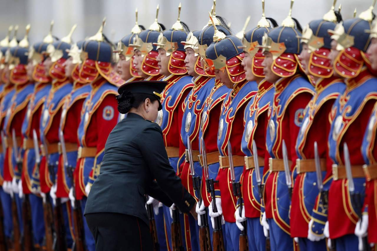 Photos of the day A member of the Mongolian army adjusts the uniforms of State Palace honor guards as they stand in line before an official welcoming ceremony for visiting German Chancellor Angela Merkel in Ulan Bator, Oct. 13, 2011. (Carlos Barria/Reuters)