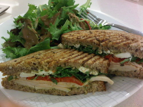 Delicious lunch sandwich: multigrain bread, avocado salsa, grilled chicken breast, goat cheese, roasted red peppers and arugula :)