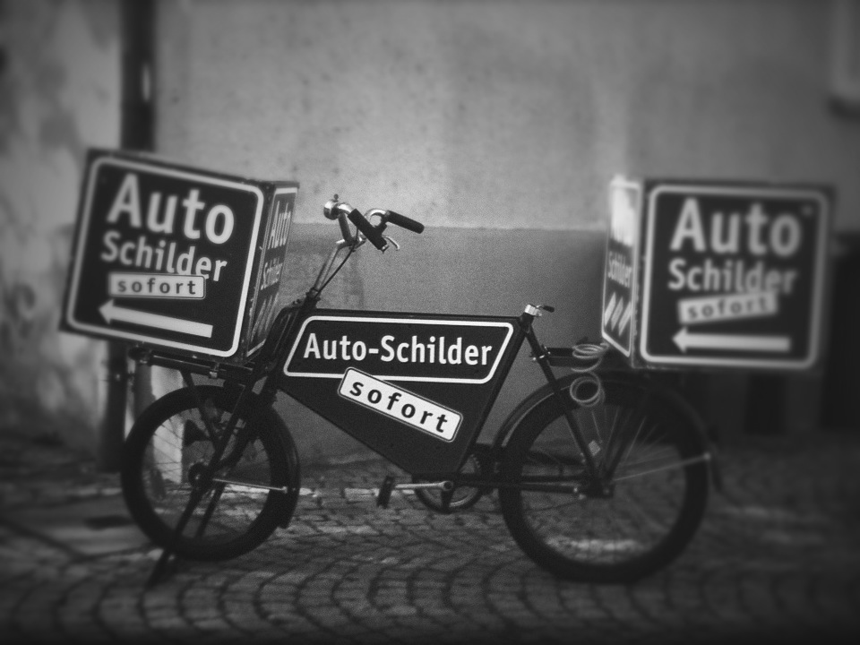 Auto schilder sofort just means fast license plates. Not so interesting but I liked all the signs on the old bike.   I used Synthcam to take this but the background wasn't blurred enough. So I desaturated it in Simply B&W and gave it a more obvious blur with TiltShiftGen.