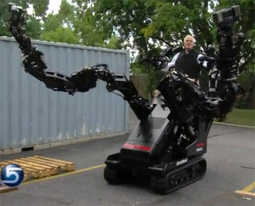 Here's a robotic machine you'd not like to meet in a dark alley. Or a well-lit one, for that matter. This is a prototype exoskeleton being developed by Raytheon-Sarcos for a variety of industrial and military uses. To really get a sense of how scary this thing looks, check out this news report, starting at the 0:15 mark:   In a way, though, this contraption does remind me a bit of the power lifter from the film Aliens. So if this thing can help us fight off acid-bleeding killer aliens then I guess I'm all for it.