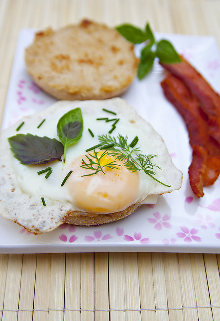 Bacon, egg, basil, dill, and chives on a toasted English muffin.