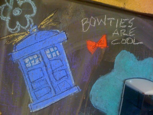 "I drew a TARDIS on the chalkboard in my art class a while ago, and the other day I came back to find that someone had added a bow tie, noting that it was cool, and ""Love form The Doctor - 1969"":  So, of course, I had to draw a bit back.  There's a Dalek saying EXTERMINATE, and a crack in the wall…  The whole thing is awesome."