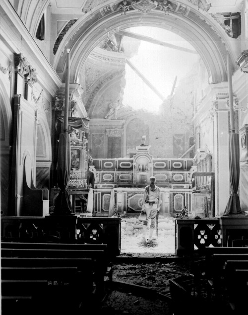 An American soldier soldier standing at the altar of a bombed out Catholic church during WWII. Acerno, Italy - September 23, 1943