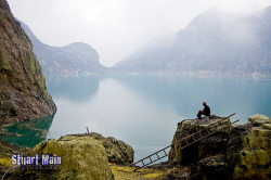 Ijen Sulpher Lake | East Java - Indonesia   After finally making it down the inside of the crater our guide waits patiently for us to recover and look around before we start the long trek back up out of the crater and down the side of the volcano. The crater lake was an incredibly deep turquoise and the yellow on the rocks is the sulpher deposit left by the clouds of toxic gases released by this active volcano. (by GrumpyShrimp)