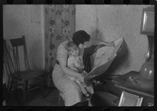 Child on lap of mother reading the newspaper. Nissen shack near Dickens, Iowa. Lee, Russell, 1903-1986, photographer. CREATED/PUBLISHED 1936 Dec.