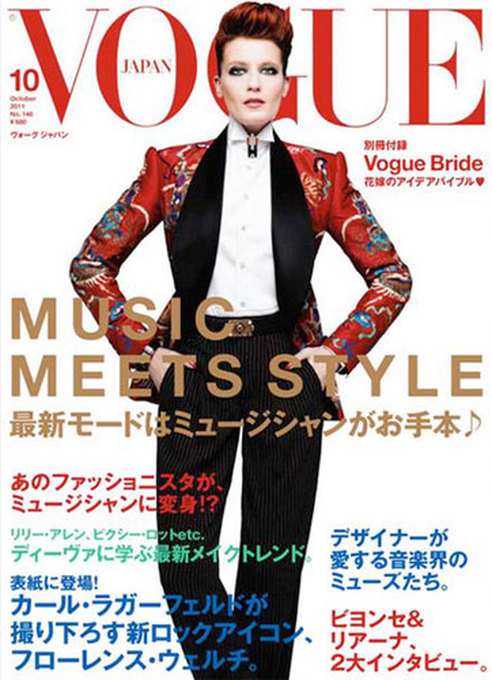 Florence Welch covers Vogue Nippon October 2011 issue. Photographed by none other than Karl Lagerfeld, Florence Welch is looking rather androgynous, wearing a suit with her fiery red hair worn up in pompadour hairstyle. Styled by Karl Lagerfeld, the Florence and  the Machine singer is showing off her unconventional look in Gucci  ensemble including crisp white shirt with black pinstripe trousers and a red patterned silk jacket. Making her look quite different is her signature flowy hair held  together in a quiff. Florence is the first non-model to front Vogue  Japan magazine in last 5 years and is looking stunning and almost  unrecognizable as mag's October 2011 cover girl.