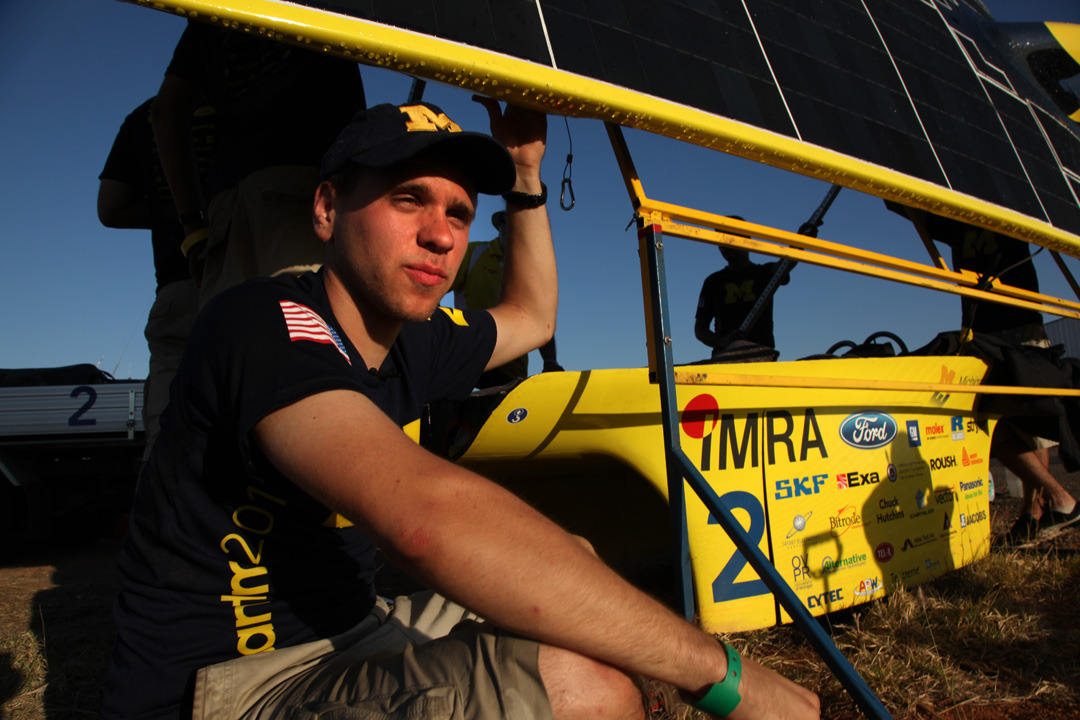 Ryan Mazur, U-M solar car driver admires the sunset as he is helping the team charge solar car panel at  the end of day three of the World Solar Challenge.  Photo by Marcin Szczepanski, Multimedia Content Producer/College of Engineering, U-M