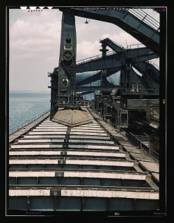"Pennsylvania R.R. iron ore docks, unloading ore from a lake freighter by means of ""Hulett"" ore unloaders (LOC) by The Library of Congress on Flickr.Via Flickr: Delano, Jack"" photographer. Pennsylvania R.R. iron ore docks, unloading ore from a lake freighter by means of ""Hulett"" ore unloaders 1943 May  1 transparency : color.Notes: Title from FSA or OWI agency caption. Transfer from U.S. Office of War Information, 1944.Subjects: Pennsylvania Railroad  World War, 1939-1945 Ore industry Shipping Railroad freight cars Machinery United States—Ohio—Cleveland Format:  Transparencies—ColorRights Info:  No known restrictions on publication.Repository:  Library of Congress, Prints and Photographs Division, Washington, D.C. 20540 USA, hdl.loc.gov/loc.pnp/pp.printPart Of:  Farm Security Administration - Office of War Information Collection 12002-16 (DLC)   93845501 General information about the FSA/OWI Color Photographs is available at hdl.loc.gov/loc.pnp/pp.fsacPersistent URL:   hdl.loc.gov/loc.pnp/fsac.1a34838Call Number:  LC-USW36-676"