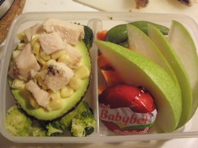 Avocado stuffed with grilled chicken and corn, veggie sticks, Baby Bel cheese, and pear slices.