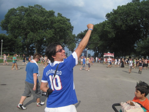 Photo subject: Indie dad wearing Bonnaroo commemorative shirt at Lollapalooza for street cred/as conversation starter Where to find him: Following the music, dude. Team: 2010 Bonnaroo Music and Arts Festival, the ninth incarnation of Tennessee's giant extravaganza. The year's team was captained by Jay-Z, Dave Matthews, Leon King, and Stevie Wonder. Aging star Conan O'Brien — winding down his self-pity tour/media blitz — featured as a late substitute.  American connection(s): Well traveled music fan shows his son (bottom right) the United States of America one huge musical gathering at a time. Six-year-old now convinced the US population is one homogenous unit of white, 20-something, progressives.