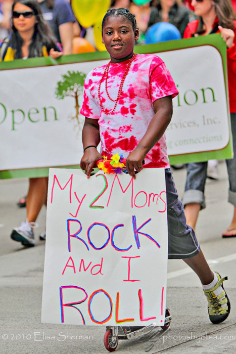 African American girl on roller skates at a pride event, holding a sign that reads, 'My 2 Moms ROCK and I ROLL!'