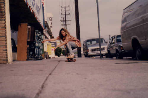 "flowerscrackconcrete:  Kim Gordon on a skateboard in front of Spinhead Studios during recording of ""Made in USA"" (North Hollywood, 1986) Photo by David Markey"