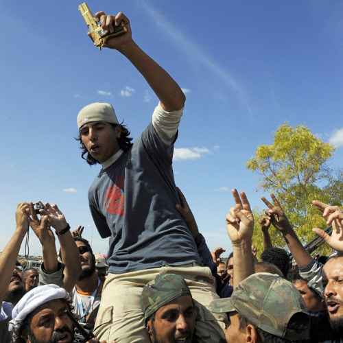 "Pictured is a man claiming to hold what was reportedly once Qaddafi's golden gun. The Guardian points to this image, available via AFP and Getty Images, that's described as ""Libyan National Transitional Council (NTC) fighters carry a young man holding what they claim to be the gold-plated gun of ousted Libyan leader."" A BBC correspondent reported earlier that the man found Qaddafi hiding, and the leader said to him: ""Don't Shoot."" Read more."