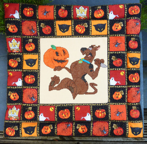 Halloween Scooby Doo  This is my second seasonal post as it's well and truly autumn in the UK now and getting close to Halloween. I made this a few years ago when it was dark and cold outside.   I've always loved Scooby Doo and I thought this image of him carving a pumpkin then scaring himself with it was pretty cool :-)  I embroidered the centre panel using cross-stitch by hand, then I found some brilliant Halloween fabric to stitch and create a soft, quilted frame.    Scooby Dooby Dooooooo