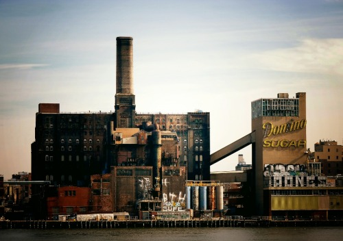 "nythroughthelens:  Domino Sugar Factory illuminated by sunlight. Williamsburg, Brooklyn. New York City. There is something remarkably touching about urban decay. It is as if sorrow and longing can be traced in the peeling layers and crumbling brick. In warm sunlight, the rich colors created by iron oxidation produce the most beautiful textures on old pipes and metal framework. The memory of those who graced the intricate insides of these structures is delicately preserved by the faded remnants that remain. During the period following the Civil War, New York was the top provider of refined sugar to the United States, and for a period of time the Domino Sugar factory in Williamsburg, Brooklyn was the largest sugar refinery in the world. At one time, the factory employed over 4,000 workers and processed 3 million pounds of sugar a day. After nearly 150 years of service, the factory shut down in 2004 due to a decline in demand. There is a new plan for this space to make it a residential space which is being actively protested by groups like the Waterfront Preservation Alliance and the Landmarks Conservancy who believe that huge development in this space would destroy the history and architectural legacy of the sugar factory. I am inclined to agree with their assessment. —- View this photo larger and on black on my Google Plus page —- Buy ""Oxidation - Domino Sugar Factory - New York City"" Posters and Prints here, email me, ask for help, or subscribe to the mailing list."