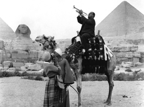 "© AP Photo, Jan. 28, 1961, Cairo / Egypt Louis ""Satchmo"" Armstrong, atop a camel, enchants the ancient sphinx and pyramids at Giza. His wife Lucille, lower left, records the scene on film. The Armstrongs are on a U.S. State Department-sponsored Goodwill Tour of Africa and the Middle East. » find more photos of famous people here «"