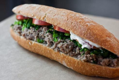 The Italian Sausage Baguette House-made Italian sausage, topped with parsley and cilantro, tomatoes and crème fraîche. Served between a warm French baguette. $9