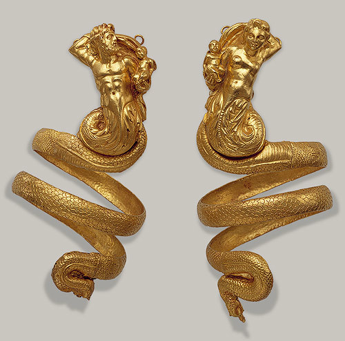 Pair of armbands, Hellenistic, ca. 200 b.c.GreekGold  These imposing serpentine armbands represent two tritons, male and  female, each holding a small winged Eros. The hoops behind the tritons'  heads were used to attach the armbands to the sleeves of a garment, for  otherwise their weight (each over 6 1/2 ounces) would have caused them  to slip down the arms.