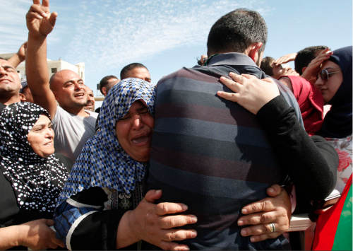 A newly released Palestinian prisoner is  greeted by a relative during a welcoming ceremony in the West Bank city  of Ramallah October 18, 2011. Israeli soldier Gilad Shalit and hundreds  of Palestinians crossed Israel's borders in opposite directions on  Tuesday as a thousand-for-one prisoner exchange brought joy to families  but did little to ease decades of conflict.   REUTERS/Abed Omar Qusini