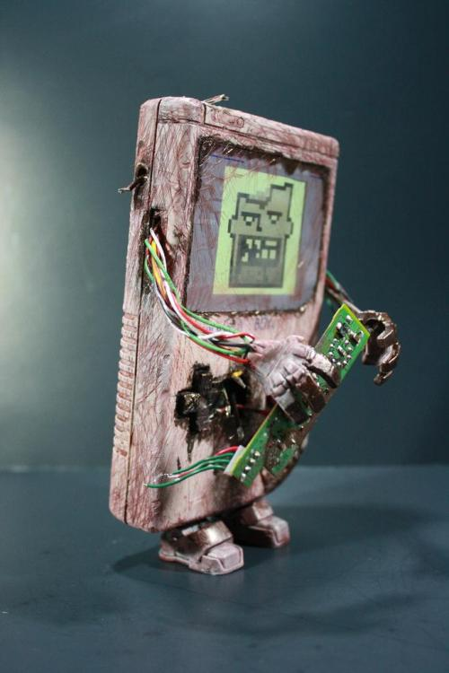 Custom Zombie Gameboy by http://www.kodykoala.com/ An old and junked Gameboy is transformed into 'Zombie Gameboy' by Kodykoala who gave the zombie a face with busted teeth, feet from an Iron Man  figure, and hands from an Iron Monger toy. The zombie's undead blood was  scribbled all over the Gameboy case with a pen containing  metallic-brown ink.