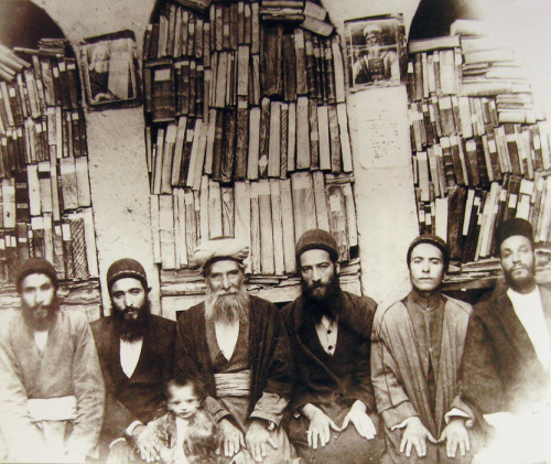touba:   Kāhen family. The mahalleh in Golpaygan, 1941. Rabbi Shemu'il Kāhen (third person from left) was educated in Iraq. He was the head rabbi in Golpaygan. The photograph was taken in his personal library, which is only partially visible here. The books, all in Hebrew, were brought to Iran from Iraq on camel back. The men's hand gesture — a gesture used by the Cohanim during the priestly benediction in the synagogue in front of the arc — signifies their status as Cohanim. The men on either side of Rabbi Shemu'il are his sons. The child is his grandson.  Photograph from Esther's Children: A Portrait of Iranian Jews, edited by Houman Sarshar.